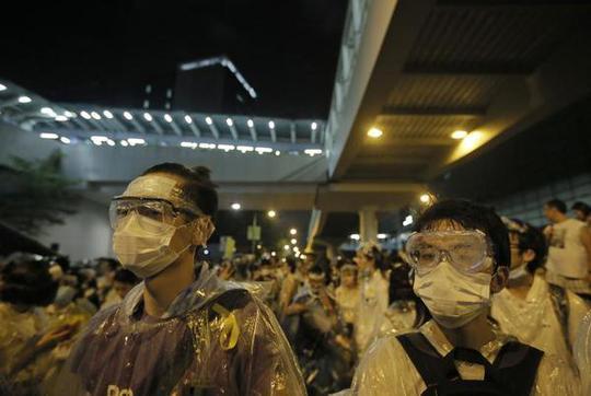 Người biểu tình tự bảo vệ trước hơi cay của cảnh sát. Ảnh: AP
