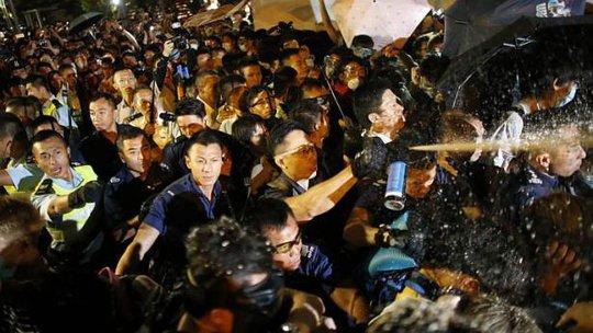 Cảnh sát xịt hơi cay vào người biểu tình rạng sáng 16-10. Ảnh: Reuters