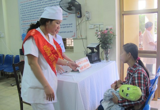 Người dân nhận phiếu khám tự động từ nhân viên y tế