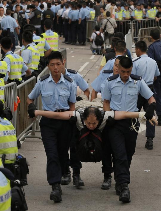 Cảnh sát bắt giữ một người biểu tình ngồi ở Hồng Kông hôm 2-7. Ảnh: AP
