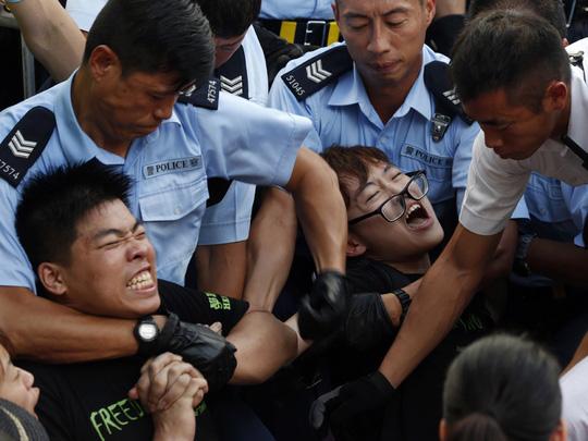 Cảnh sát tìm cách khống chế người biểu tình ngồi ở Hồng Kông hôm 2-7. Ảnh: AP