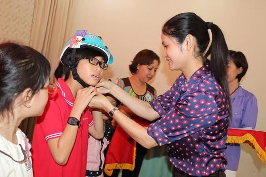 Bà Nguyễn Thu Hương, Chủ tịch LĐLĐ quận Bình Thạnh, TP HCM, tặng nón bảo hiểm cho con CNVC-LĐ khó khăn