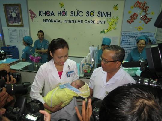 Bé sơ sinh được đưa ra gặp cha trong vòng tay của ThS-BS Phạm Thị Thanh Tâm, Trưởng khoa Hồi sức sơ sinh (trái) và TS-BS Nguyễn Thanh Hùng, Giám đốc BV Nhi Đồng 1