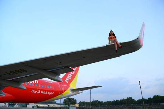 Có người mẫu mặc bikini ngồi vắt vẻo trên cánh máy bay