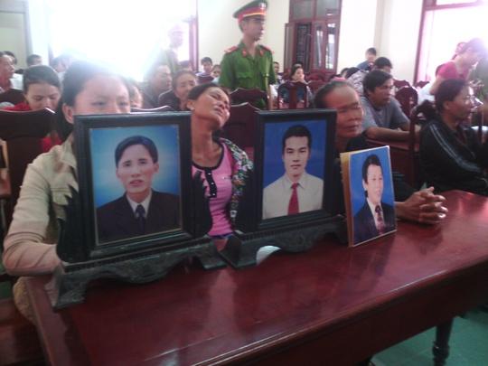 Người nhà của các nạn nhân đem di ảnh của người thân đến dự tòa