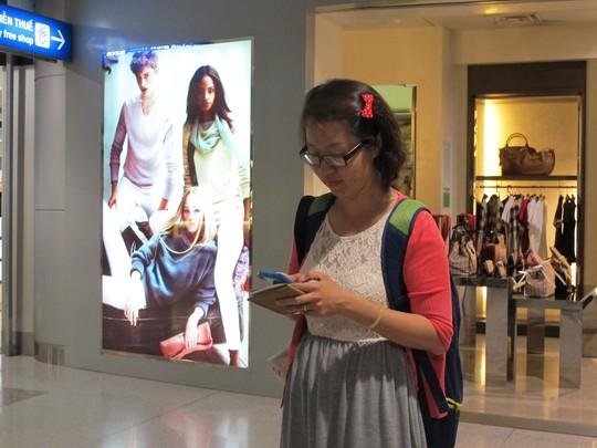 Một hành khách nhắn tin cho người thân sau khi vui vẻ cởi giày qua máy soi