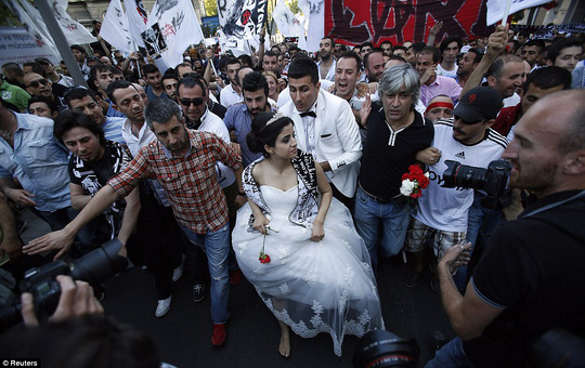 A newlywed couple joins protesters as they march towards Taksim Square in Istanbul June 8, 2013