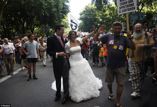 Spanish newlyweds join demonstrators as they march towards Madrid's Puerta del Sol during a protest against politicians, banks, the economic crisis and austerity measures of Europe, in Madrid July 24, 2011