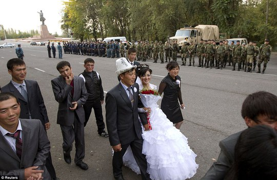 A newlywed couple walks, with Interior Ministry officers and servicemen lining up in the background, on a street in the city of the volatile city of Osh, Kyrgyzstan, October 9, 2010