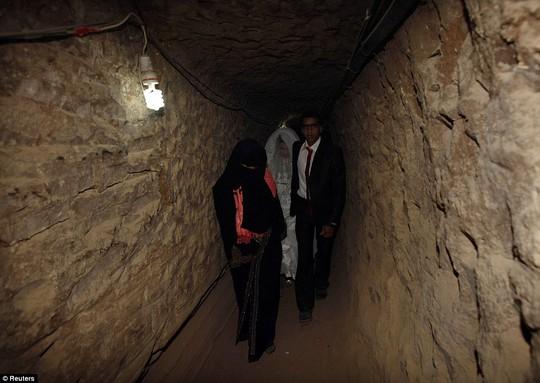 Palestinian groom Emad al-Malalha, 21, walks with Manal Abu Shanar, 17, his Egyptian bride inside a smuggling tunnel beneath the Gaza-Egypt border in the southern Gaza Strip on March 21, 2013