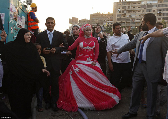 A newlywed couple, supporters of deposed Egyptian President Mohamed Mursi, at Raba' al-Adawya mosque, celebrating with protesters, east of Cairo, August 12, 2013