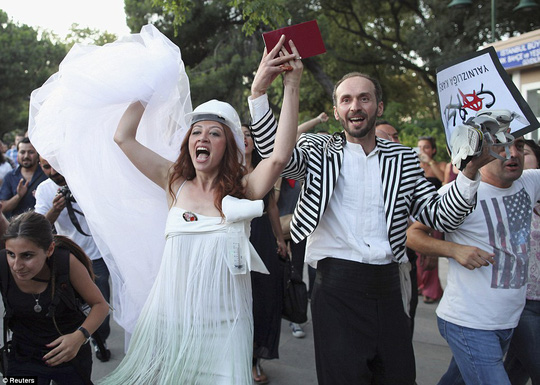 Newly married couple Nuray Cokol and Ozgur Kaya shout slogans as they visit Gezi Park after their wedding ceremony in Istanbul July 20, 2013