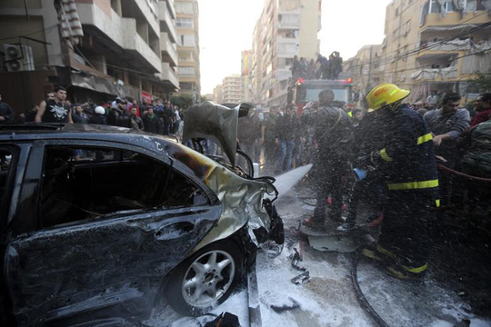 A firefighter extinguishes a fire on a car at the site of an explosion in Beirut's southern suburbs