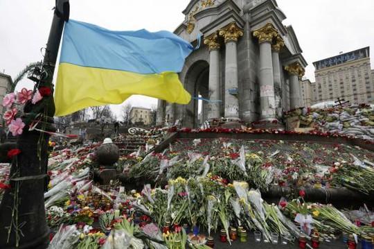 Ukraines national flag flies at a make-shift memorial for those killed in recent violence in Kiev February 25, 2014. REUTERS-Konstantin Chernichkin