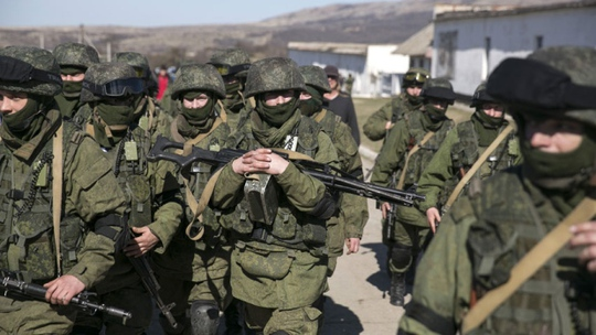 Military personnel, believed to be Russian servicemen, walk outside the territory of a Ukrainian military unit in Crimea. A Ukrainian mission to the United Nations claims 16,000 Russian troops have massed in Crimea.