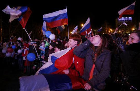 People celebrate and wave Russian flags as the preliminary results of todays referendum are announced in the Crimean city of Sevastopol March 16, 2014. REUTERS-Baz Ratner
