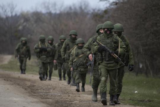 Armed men, believed to be a Russian servicemen, walk as they change shifts near a military base in Perevalnoye, near the Crimean city of Simferopol, March 20, 2014. REUTERS/Baz Ratner