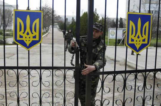 A Ukrainian soldier closes an entrance gate at the airforce base in the Crimean town of Belbek March 20, 2014. REUTERS-Shamil Zhumatov
