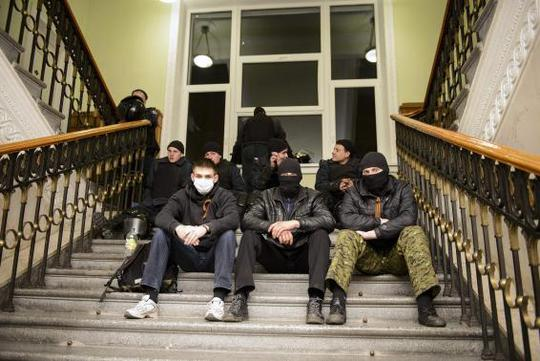 Pro-Russian protesters sit inside the seized regional administrative building in Kharkiv April 6, 2014. REUTERS-Stringer
