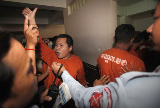 A man (C) convicted of plotting to overthrow the Cambodian government shouts after being sentenced at the Phnom Penh Municipal Court April 11, 2014. REUTERS-Samrang Pring