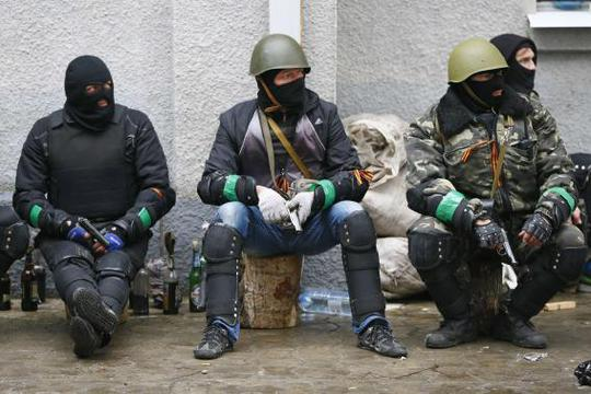 Pro-Russian armed men sit near the police headquarters in Slaviansk April 13, 2014. Ukraines Interior Minister on Sunday told residents in the eastern city of Slaviansk to stay indoors, in anticipation of clashes between pro-Russian militants who have seized official buildings and Ukrainian security forces. REUTERS-Gleb Garanich