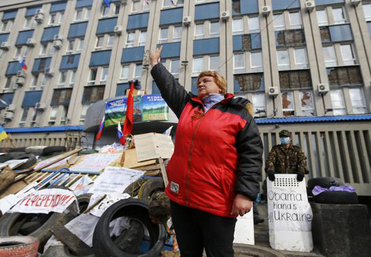 A pro-Russian protester gestures at a barricade in front of the seized office of the SBU state security service in Luhansk, in eastern Ukraine April 14, 2014. REUTERS-Shamil Zhumatov