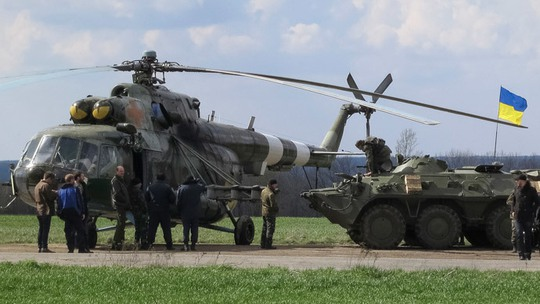 Ukrainian soldiers are seen near a MI-8 military helicopter and armored personnel carrier at a checkpoint near the town of Izium in Eastern Ukraine, April 15, 2014. (Reuters / Dmitry Madorsky)