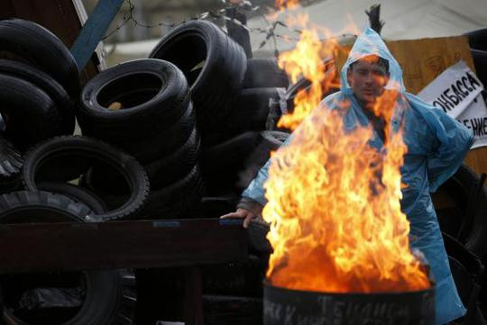 A pro-Russia protester warms himself by the fire on a barricade outside a regional government building in Donetsk, in eastern Ukraine April 20, 2014. REUTERS-Marko Djurica