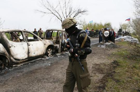 A Pro-Russian militant walks near a checkpoint that was the scene of a gunfight overnight near the city of Slaviansk, April 20, 2014. REUTERS-Gleb Garanich
