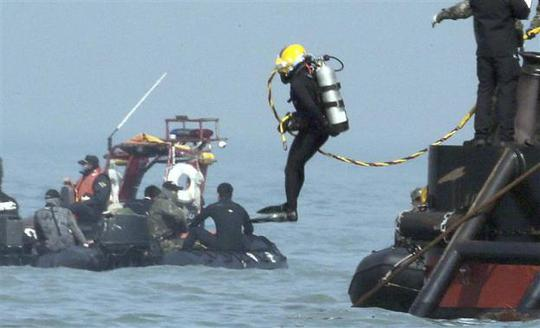 A diver jumps into the sea near an area where the capsized passenger ship Sewol sank during a rescue operation in Jindo April 24, 2014. REUTERS-Yonhap