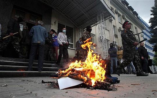 Pro-Russian activists burn Ukrainian symbols in front of the occupied Office of Public Prosecutor in Lugansk, Ukraine