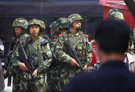 Paramilitary policemen stand guard near the exit of the South Railway Station, where three people were killed and 79 wounded in a bomb and knife attack on Wednesday, in Urumqi, Xinjiang Uighur Autonomous region, May 1, 2014. REUTERS-Petar Kujundzic