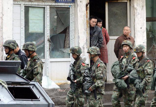 Armed policemen patrol past a building whose window was damaged by an explosion in Urumqi, northwest Chinas Xinjiang region, on Thursday.