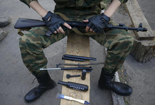 A pro-Russian armed man, with the parts of his weapon laid out on a bench, poses for a picture at a checkpoint in Slaviansk, eastern Ukraine May 23, 2014. REUTERS/Maxim Zmeyev