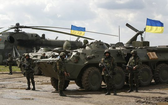 ukrainian-soldiers-stand-at-armored-personnel-carriers-with-ukrainian-flags-in-the-back-as-ukrainian-army-troops-receive-ammunition-in-a-field-on-the-outskirts-of-izyum-eastern-ukraine-on-tuesday-april-15-2014-an-associated-press-reporter-saw-at-least-14-armored-personnel-carriers-with-ukrainian-flags-one-helicopter-and-military-trucks-parked-24-miles-north-of-the-city-tuesday