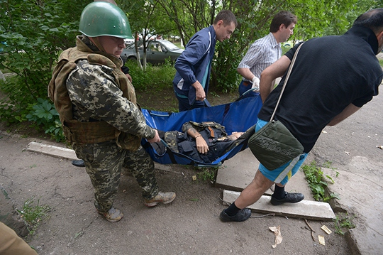 A fighter of the peoples militia and local residents evacuate a militiaman wounded during a battle with Ukraines border guards in the Mirny neighborhood on the outskirts of Lugansk (RIA Novosti / Evgeny Biyatov)