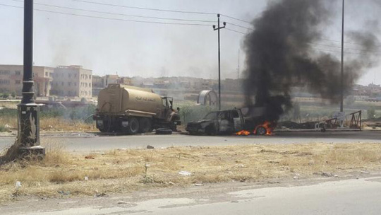 Burning vehicles belonging to Iraqi security forces are seen during clashes between Iraqi security forces and al Qaeda-linked Islamic State in Iraq and the Levant (ISIL) in the northern Iraq city of Mosul, June 10, 2014. REUTERS-Stringer