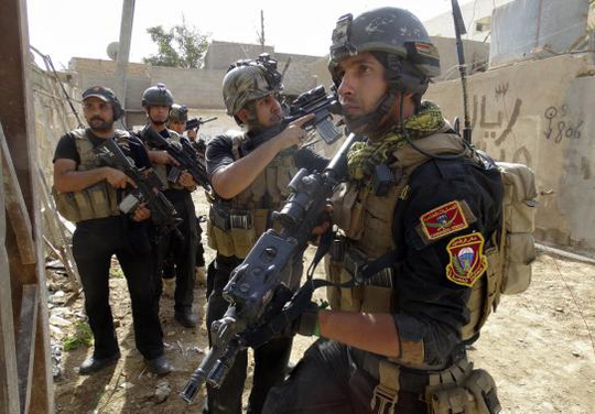 Members of the Iraqi Special Operations Forces (ISOF) take their positions during a patrol looking for militants of the Islamic State of Iraq and the Levant (ISIL), explosives and weapons in a neighbourhood in Ramadi, June 13, 2014. Picture taken June 13, 2014. REUTERS-Osama Al-dulaimi