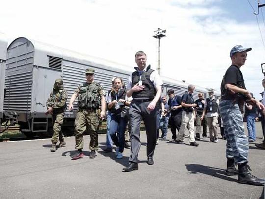 Các quan sát viên Tổ chức An ninh và Hợp tác châu Âu (OSCE) ở gần các toa xe chứa nạn nhân. Ảnh: REUTERS