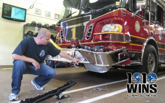 New Hyde Park Fire Chief Steven Waldron shows damage to fire truck from crash. (Photo: Mona Rivera, 1010 WINS)