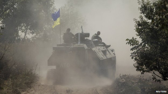 Ukrainian servicemen ride atop an armoured personnel carrier as they patrol an area near Donetsk on 11 August 2014.