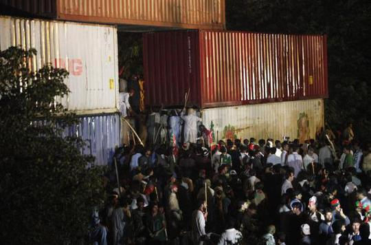 Supporters of former international cricketer Imran Khan, chairman of the Pakistan Tehreek-e-Insaf (PTI) political party, climb on container barricades as they participate during a Freedom March to the parliament house in Islamabad August 19, 2014.REUTERS-Akhtar Soomro