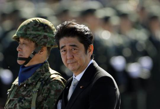 Japanese Prime Minister Shinzo Abe (R) reviews Japanese Self-Defence Forces (SDF) troops during the annual SDF ceremony at Asaka Base in Asaka, near Tokyo, in this October 27, 2013 file photo. REUTERS/Issei Kato/Files