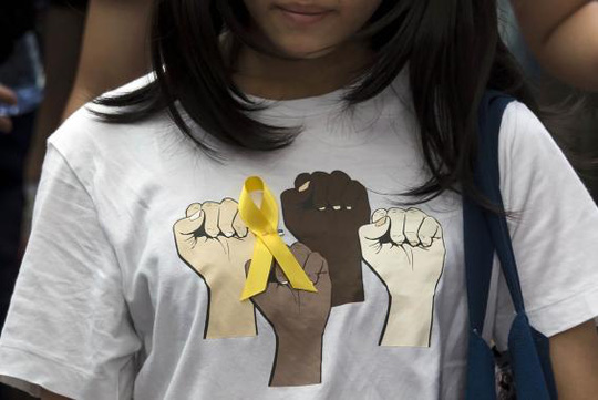 A secondary school student wears a yellow ribbon pinned to her T-shirt during a rally against Beijings election framework for Hong Kong, outside the government headquarters in Hong Kong September 26, 2014.  REUTERS-Tyrone Siu