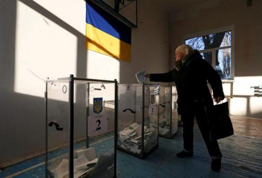 A woman casts a ballot during a parliamentary election at a school gym in the village of Semyonovka near Slaviansk, eastern Ukraine, October 26, 2014. REUTERS-Vasily Fedosenko