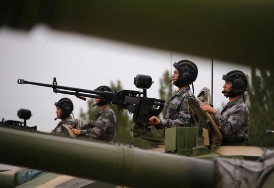 Soldiers of Peoples Liberation Army (PLA) stand inside tanks at a drill during an organised media tour at a PLA engineering academy in Beijing July 22, 2014. REUTERS/Petar Kujundzic