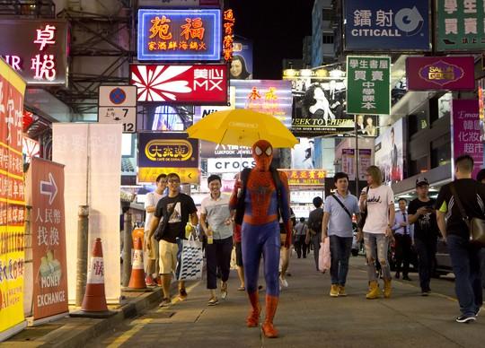 Người nhện cầm dù rảo bước trên đường phố khu Mongkok. Ảnh: WORLD POST