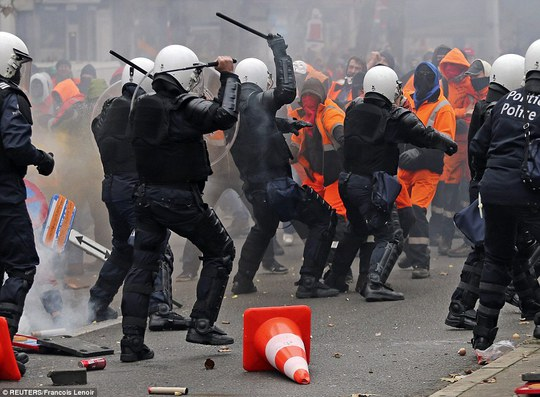 Riot police use their batons to beat back protesters after a mass demonstration against austerity measures in Brussels, Belgium