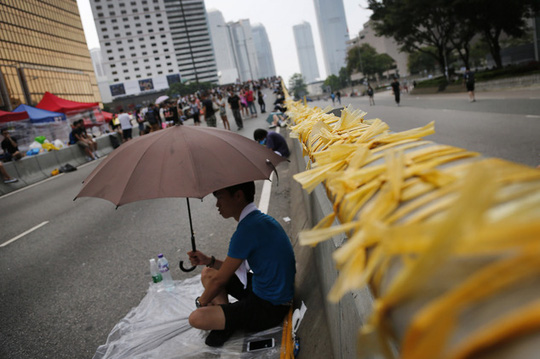 A pro-democracy protester leans against a street divider covered with yellow ribbons, which have become a symbol for people to show their solidarity with pro...