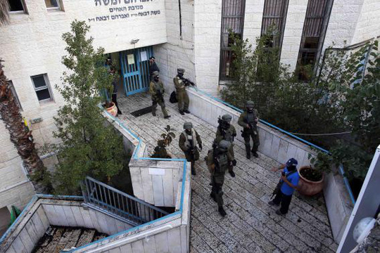 Israeli security personnel search a religious Jewish Yeshiva next to a synagogue, where a suspected Palestinian attack took place, in Jerusalem, November 18, 2014. REUTERS-Ronen Zvulun